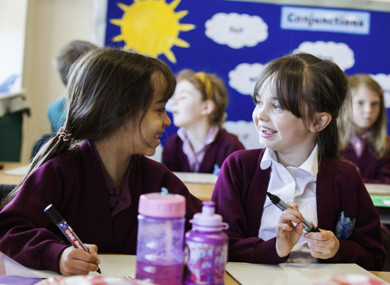 Two pupils, sat at their desks, smiling at each other.