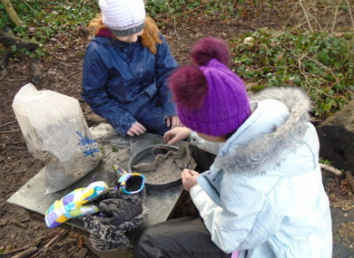 Two girls making something with clay in Forest School.